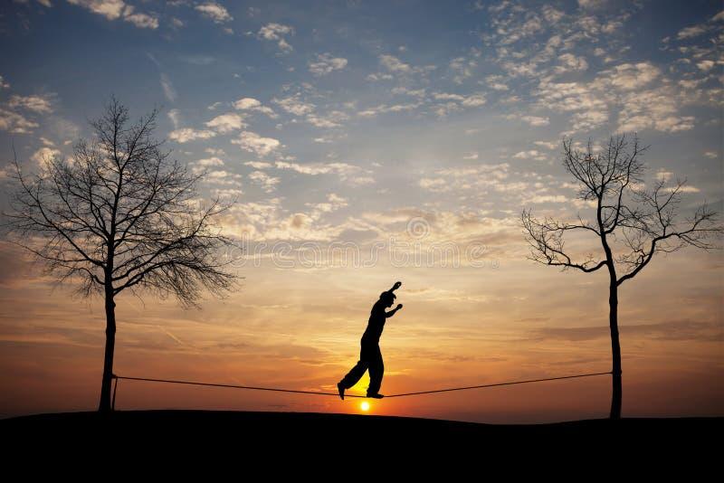 Силуэт человека на slackline стоковая фотография