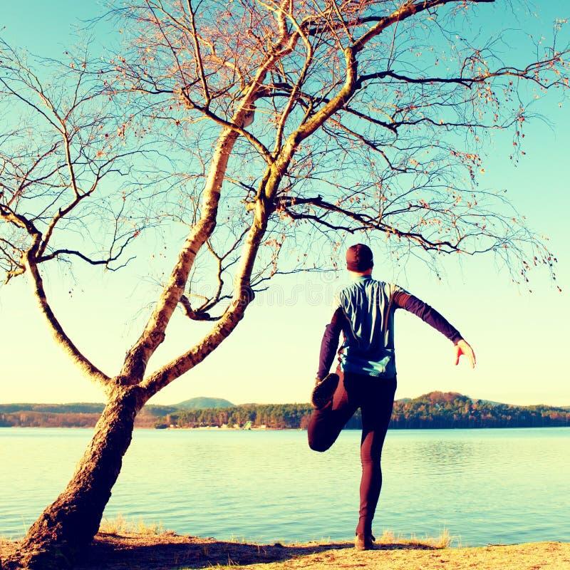 Силуэт человека спорта активного в идущих leggins и голубой рубашки на дереве березы на пляже Спокойная вода, остров и солнечный  стоковая фотография