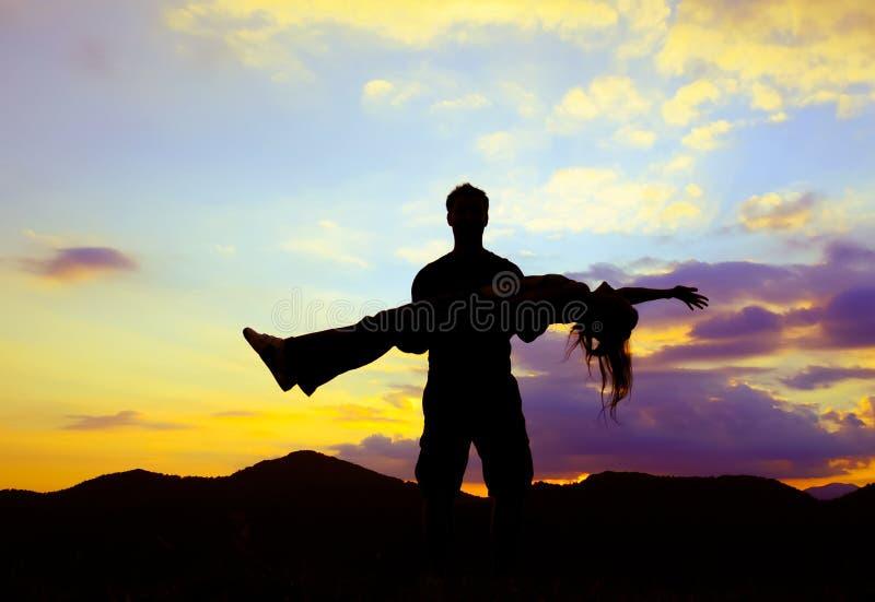 Силуэт человека стоя и держа женщина вверх na górze горы стоковое изображение rf