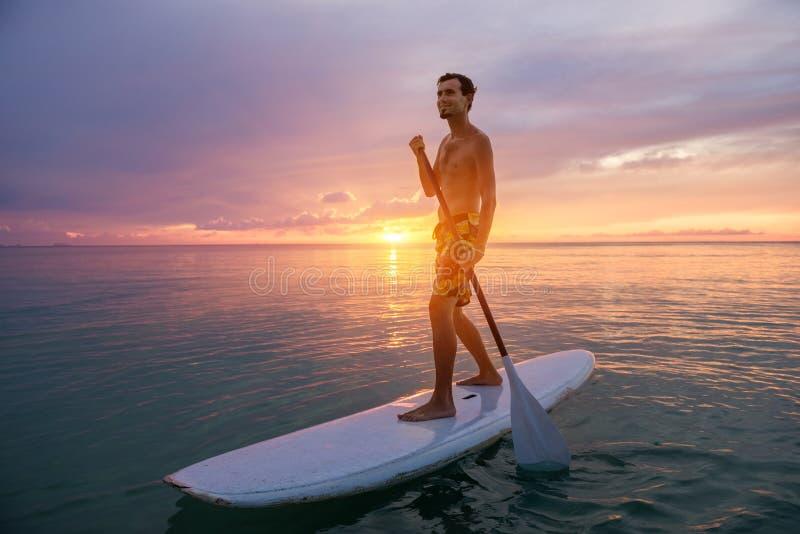 Силуэт человека Paddleboarding на заходе солнца стоковые изображения rf