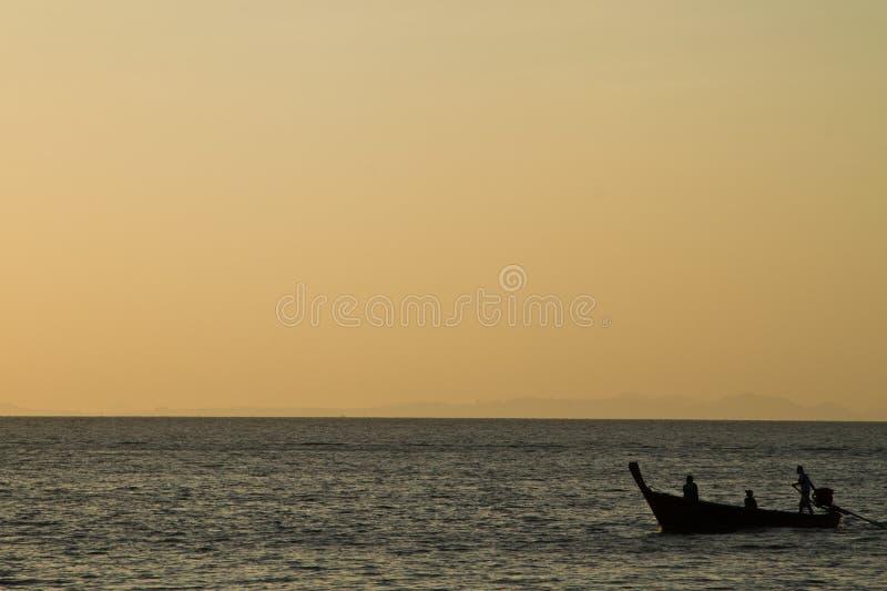 Силуэт шлюпки длинного хвоста в пляже Таиланде Railay на заходе солнца стоковые изображения