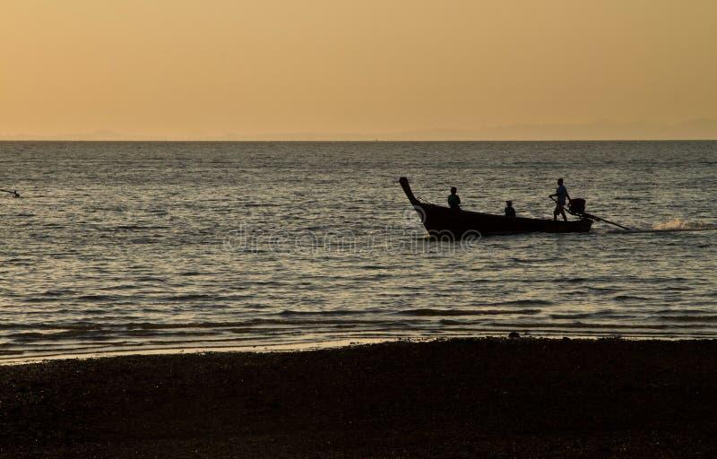 Силуэт шлюпки длинного хвоста в пляже Таиланде Railay на заходе солнца стоковые изображения rf