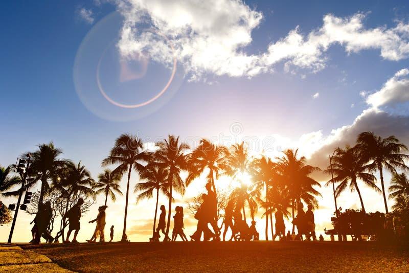 Силуэт людей идя на заход солнца на толпить Waikiki стоковое фото rf