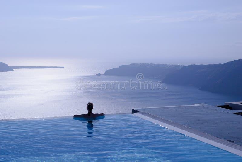 Силуэт Emale в пейзажном бассейне на скале, Santorini, Греции стоковая фотография rf