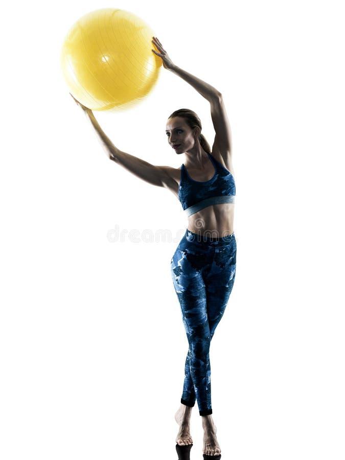Силуэт excercises шарика фитнеса женщины швейцарский стоковое фото