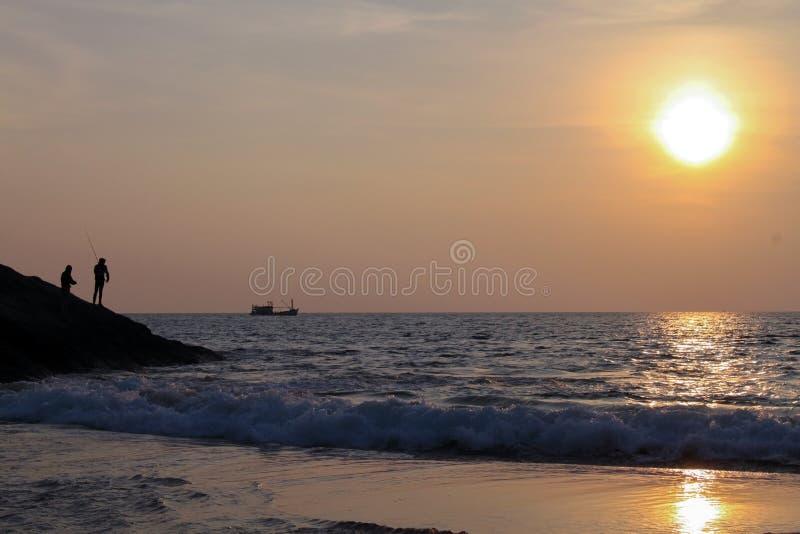 Силуэт fisher на заходе солнца на seashore стоковые изображения
