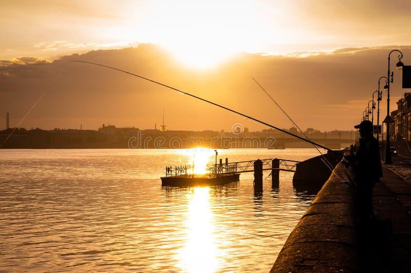 Силуэт fisher с желать штангу на банке реки Neva стоковое фото