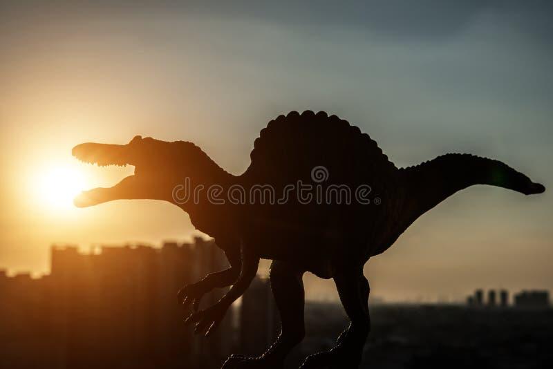 Силуэт spinosaurus и зданий во времени захода солнца стоковые фото