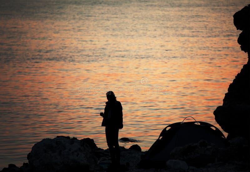 Силуэт trekker на шатре скалистого seashore близко располагаясь лагерем на ove стоковые изображения rf