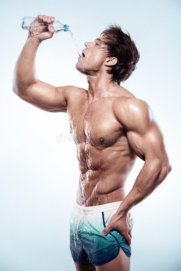 Сильная атлетическая питьевая вода человека и показывать большой бицепс стоковое фото