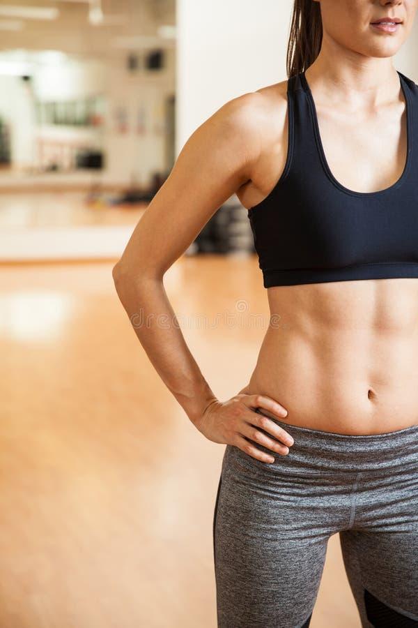 Сильная женщина с тонизированным abs на спортзале стоковое изображение rf