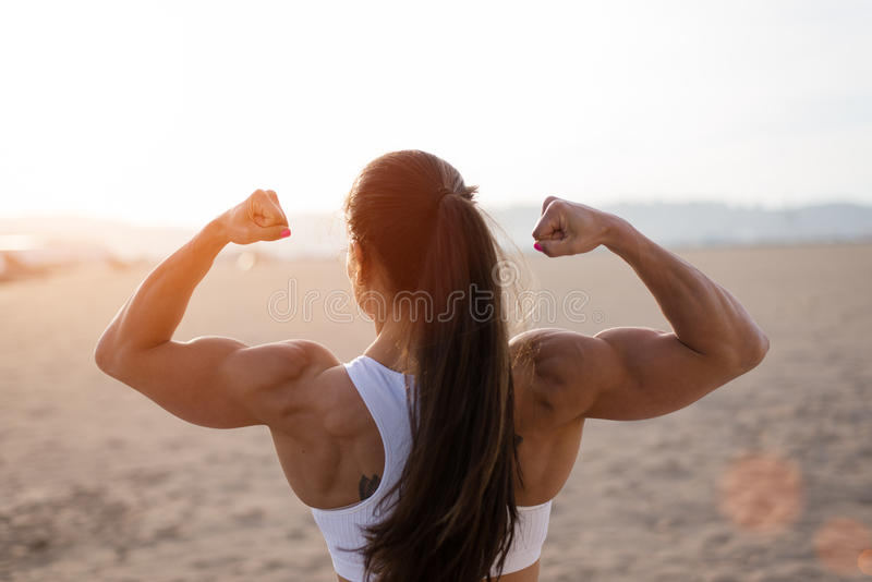 Сильная женщина фитнеса изгибая бицепс на заходе солнца стоковое фото rf