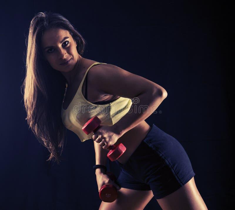 Сильная молодая женщина делая отскоки гантели стоковое изображение rf
