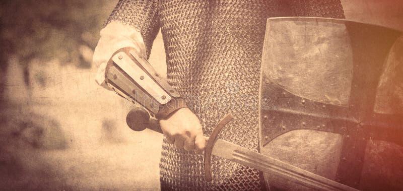 Сильная рука рыцаря с красивыми шпагой и экраном на середине стоковые фотографии rf