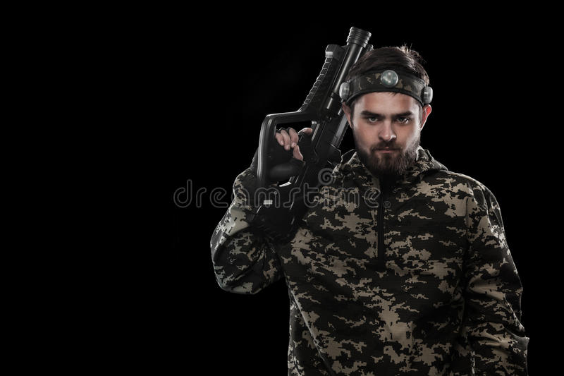 Сильно вооруженный замаскированный солдат пейнтбола изолированный на черной предпосылке Концепция объявления стоковое фото