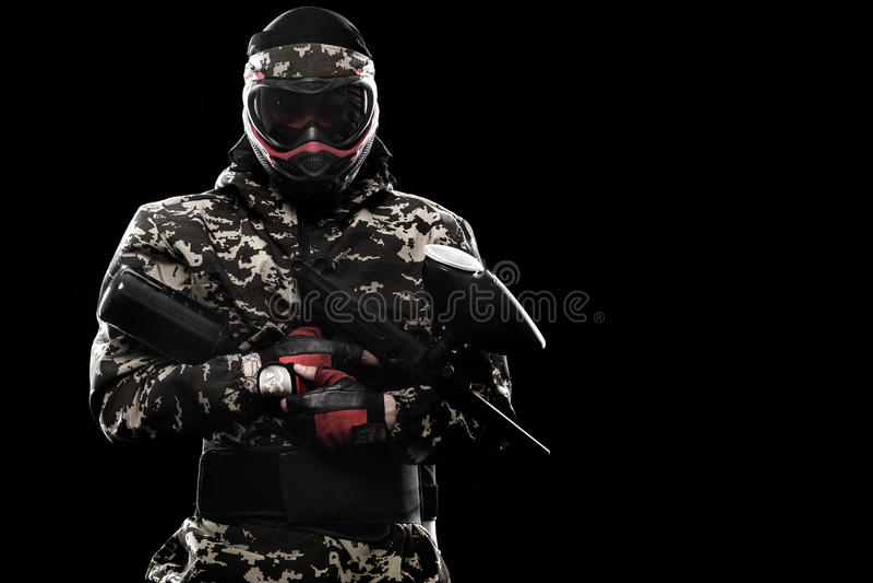 Сильно вооруженный замаскированный солдат пейнтбола изолированный на черной предпосылке Концепция объявления стоковое фото rf