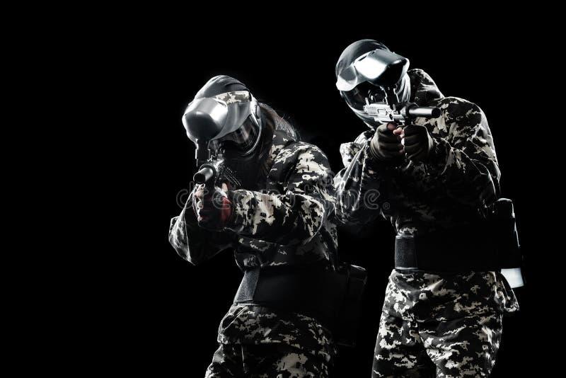 Сильно вооруженный замаскированный солдат пейнтбола изолированный на черной предпосылке Концепция объявления стоковые фотографии rf