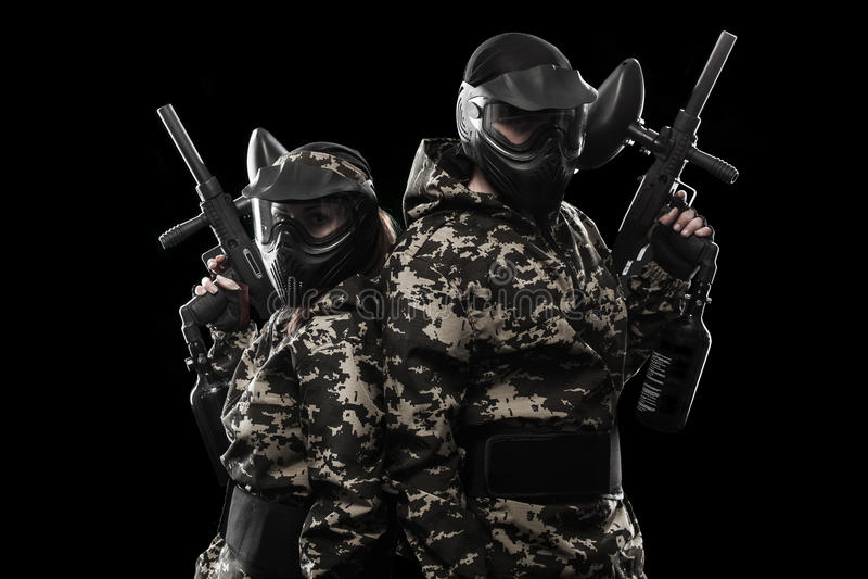 Сильно вооруженный замаскированный солдат пейнтбола изолированный на черной предпосылке Концепция объявления стоковое изображение rf