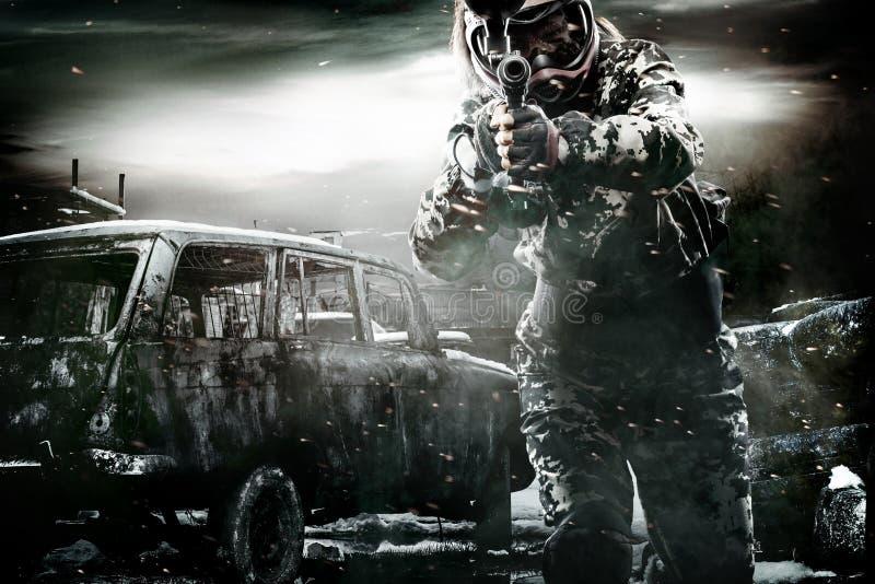 Сильно вооруженный замаскированный солдат пейнтбола на предпосылке столба апоралипсической Концепция объявления стоковые фотографии rf