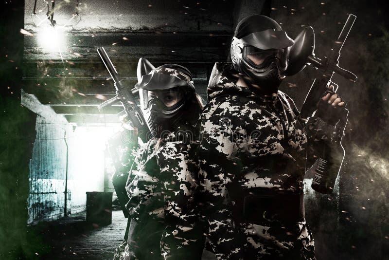 Сильно вооруженный замаскированный солдат пейнтбола 2 на предпосылке столба апоралипсической Концепция объявления стоковое фото