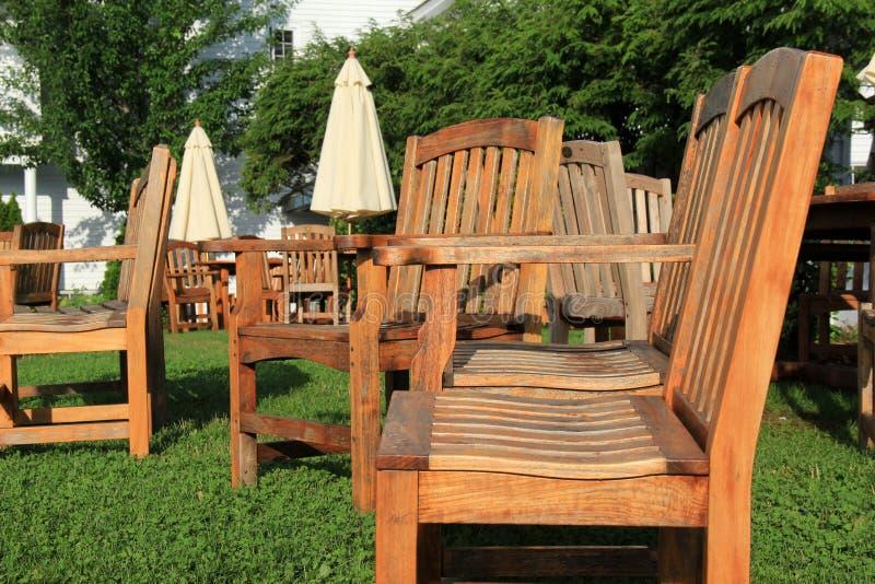 Сильно поношенная деревянная мебель и зонтики на деланной маникюр лужайке стоковая фотография rf
