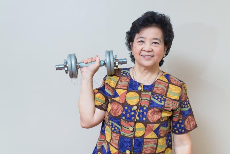Сильный азиатский старший подниматься женщины утяжеляет, в съемке студии, speci стоковые изображения rf