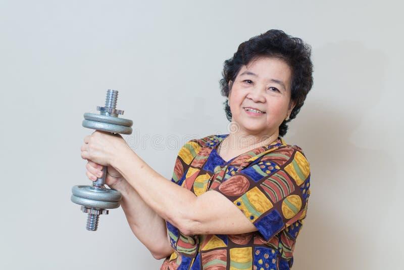 Сильный азиатский старший подниматься женщины утяжеляет, в съемке студии, speci стоковое фото rf