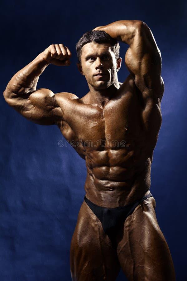 Сильный атлетический торс модели фитнеса человека показывая большие мышцы стоковое фото