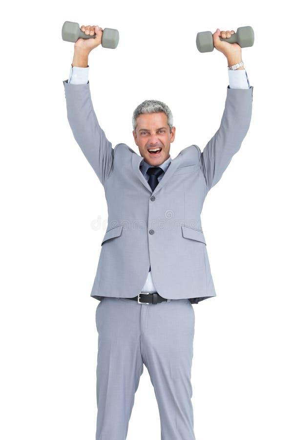 Сильный бизнесмен поднимая тяжелые гантели стоковая фотография rf