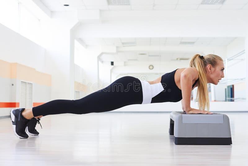 Сильный делать женщины нажимает вверх позицию разминки abdominals стоковое фото rf