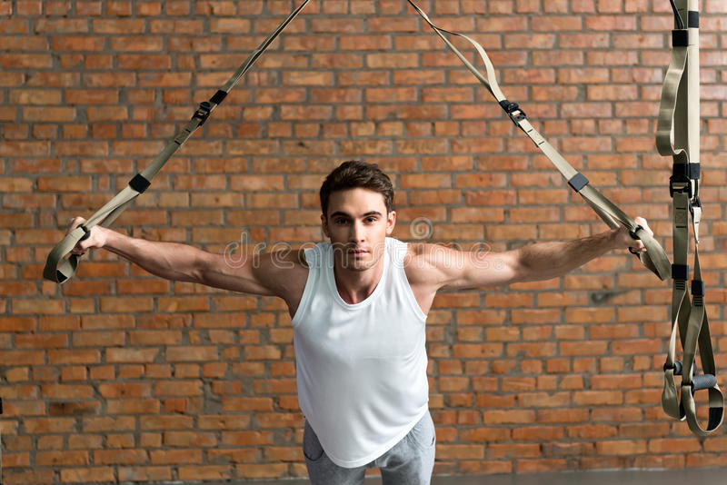 Сильный мужской делать спортсмена нажим-поднимает с эластичной резиновой лентой стоковые фото