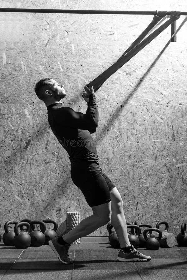 Сильный мышечный спортсмен работая с диапазоном сопротивления стоковые изображения