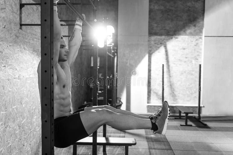 Сильный мышечный человек поднимая его ноги стоковое фото rf