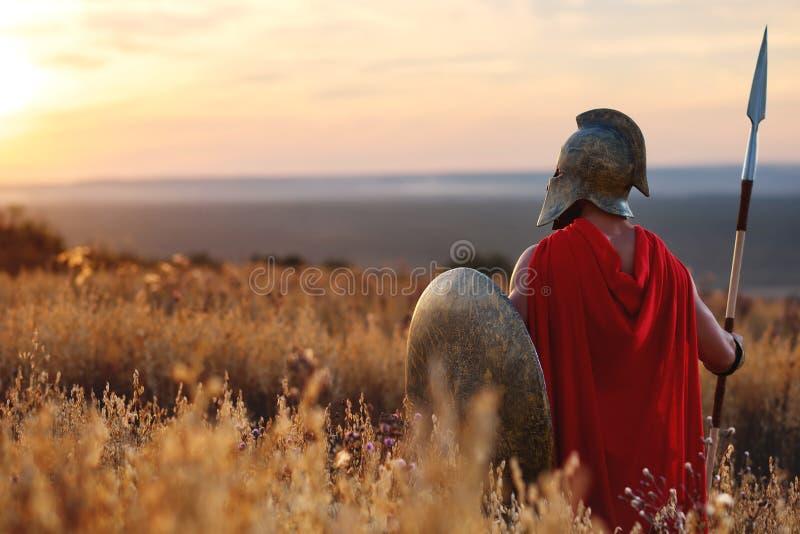 Сильный спартанский ратник в платье сражения с экраном и копьем стоковое изображение