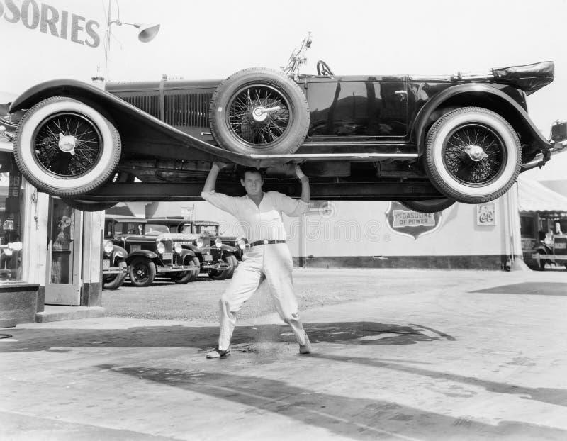 Сильный человек поднимая автомобиль над его головой (все показанные люди более длинные живущие и никакое имущество не существует  стоковое фото