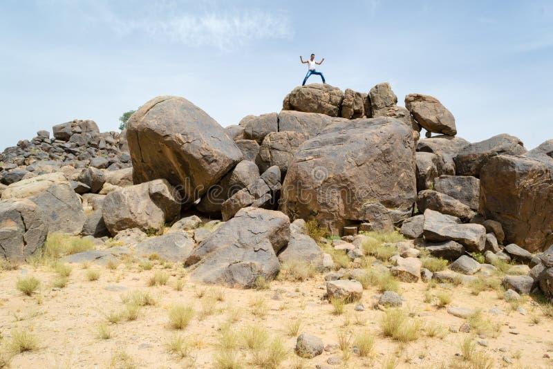 Сильный человек na górze утесов пустыни стоковое фото rf