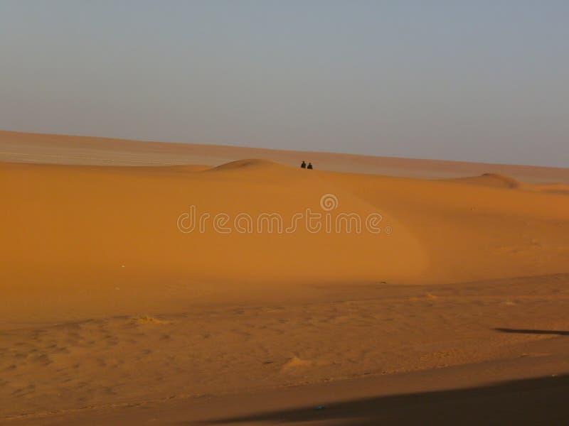 Сидящ в верхней части дюны, расточительствуя время стоковые изображения rf