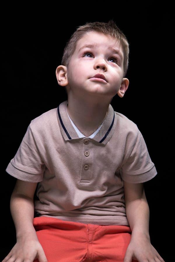 Сидя маленький белокурый мальчик смотря вверх стоковое изображение