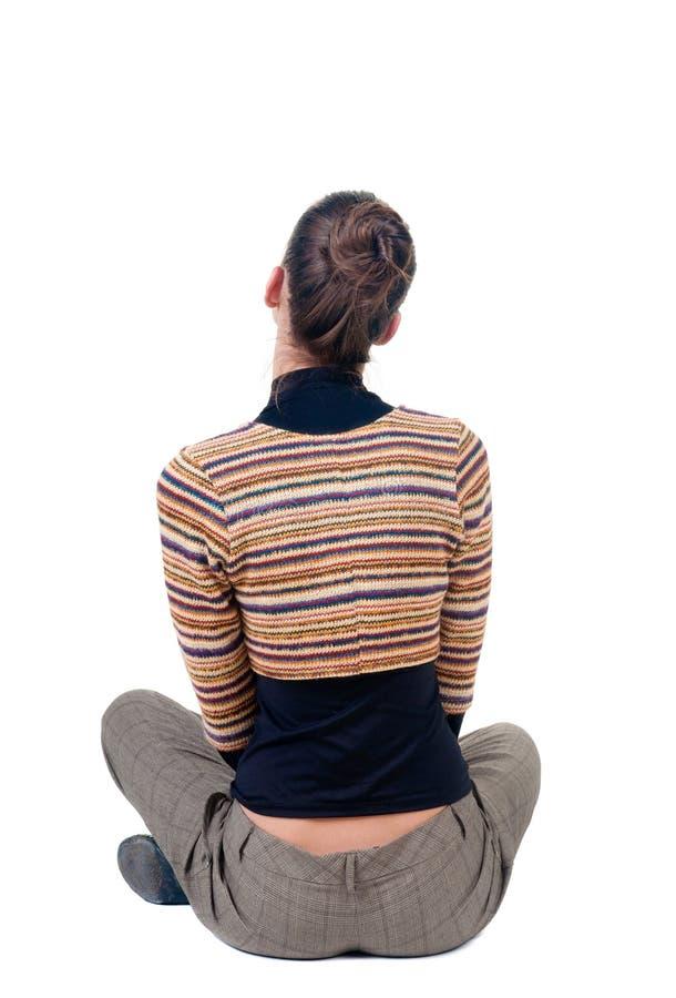 Сидя молодая женщина смотрит afar изолированная белизна вид сзади стоковое изображение rf