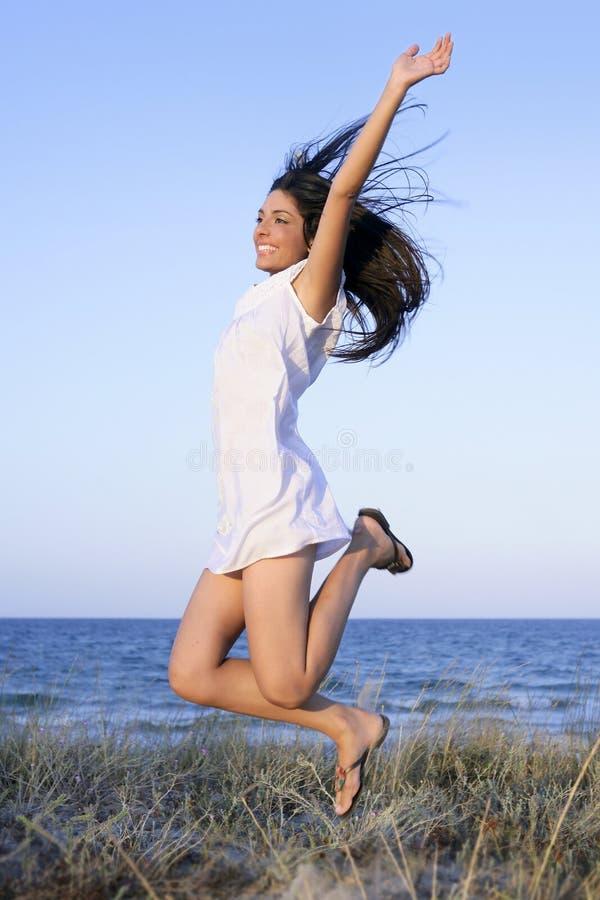 скакать брюнет пляжа красивейший стоковая фотография