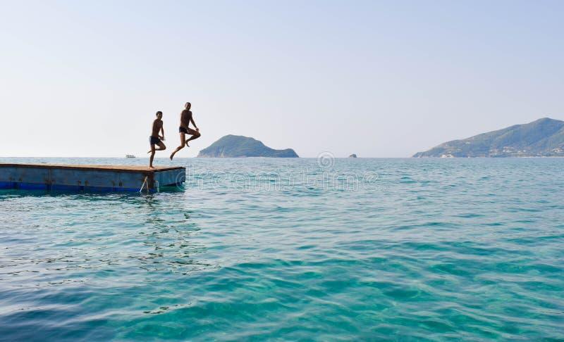 Скакать в море от понтона стоковые фото