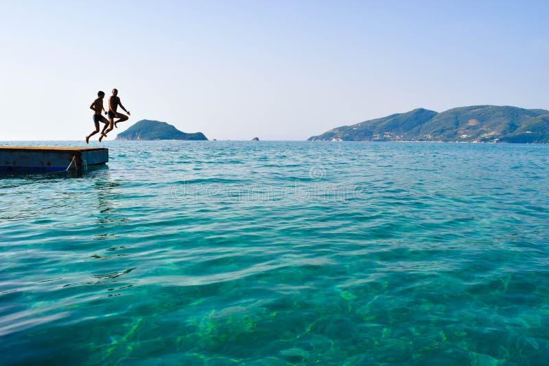 Скакать в море от понтона стоковое фото rf