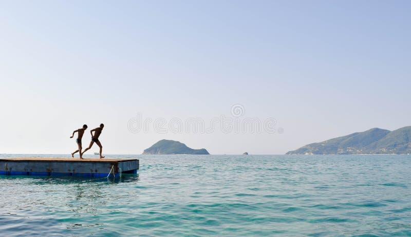 Скакать в море от понтона стоковая фотография
