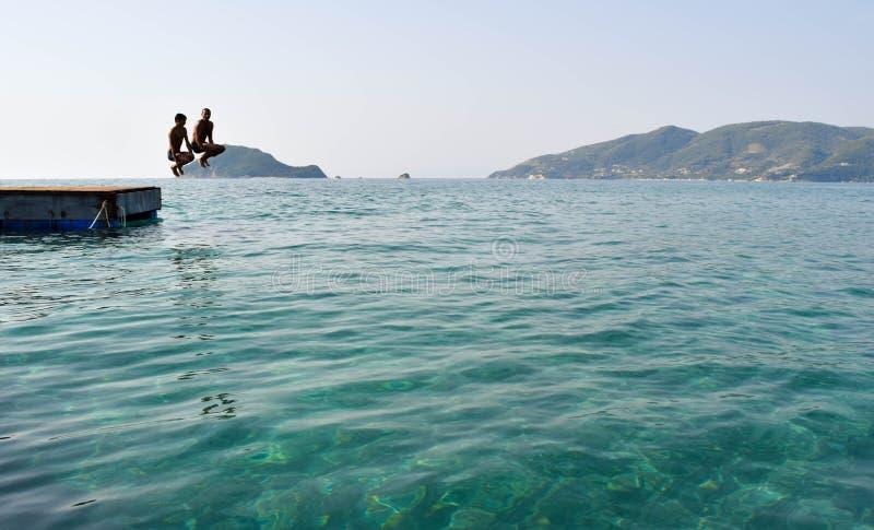 Скакать в море от понтона стоковые изображения