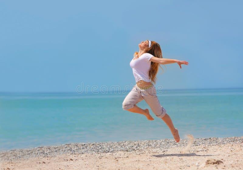 скакать девушки пляжа счастливый стоковые фото