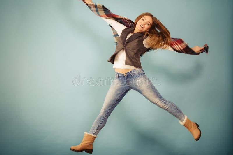 Скакать девушки осени моды женщины, летая в воздух на сини стоковая фотография