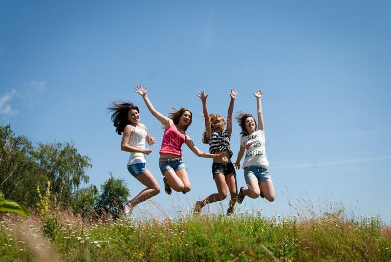 Скакать 4 красивый счастливый предназначенный для подростков подруг стоковое фото rf