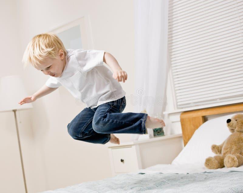 скакать мальчика спальни воздушного матраса средний стоковые изображения