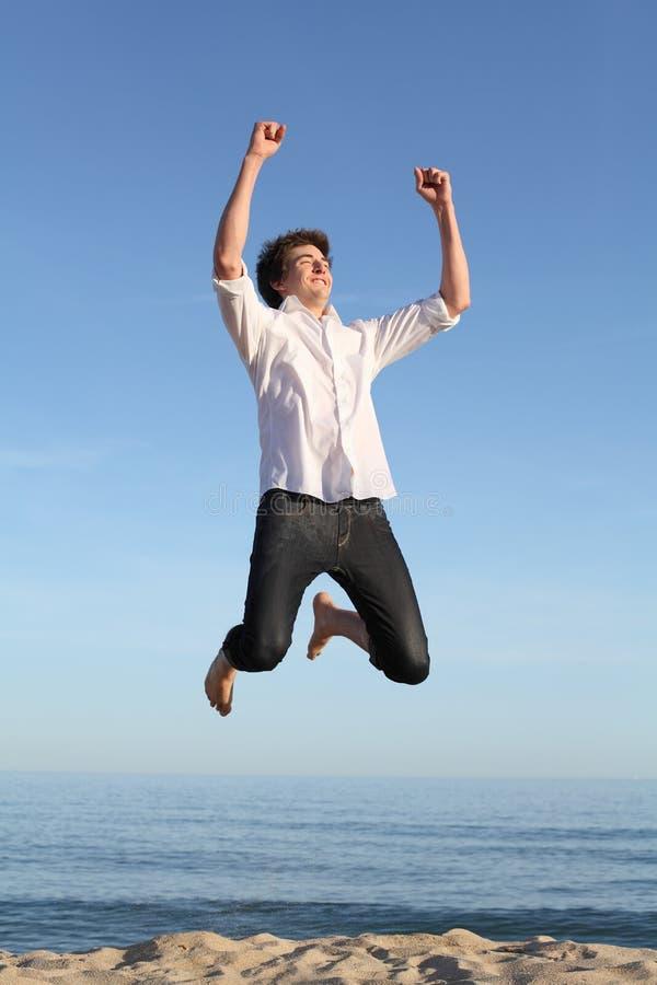 Скакать мальчика счастливый на пляже стоковая фотография