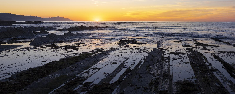 Скалистое побережье Zumaia, захода солнца colorfull над пляжем sakoneta стоковое фото